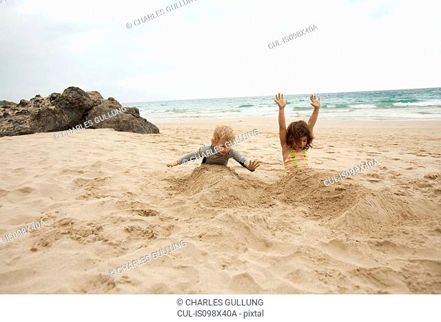 Boy and girl buried in sand on beach