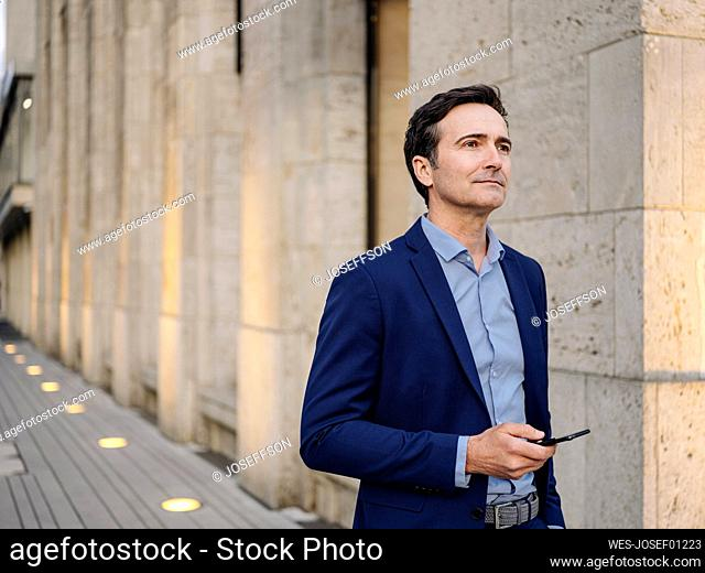 Thoughtful mature businessman with smartphone in the city