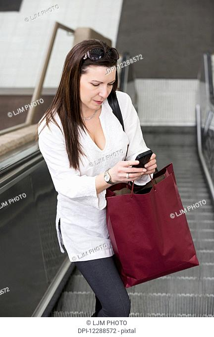 Business woman texting on her smart phone on an escalator after taking a shopping break during her work day; Edmonton, Alberta, Canada