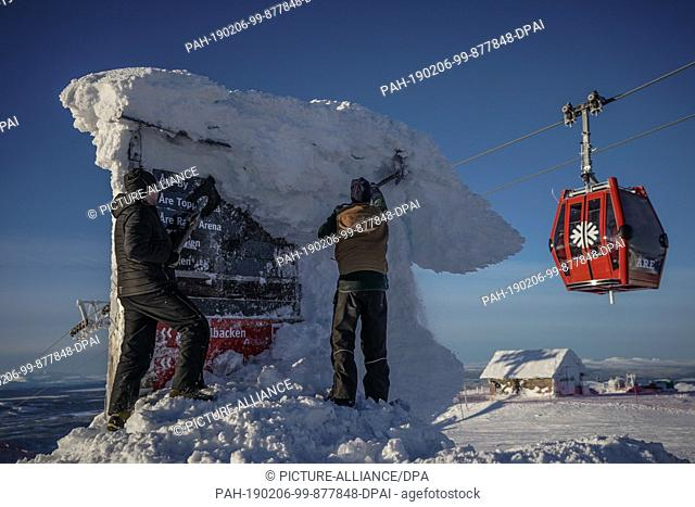 22 January 2017, Sweden, Are: Alpine skiing, World Championships, Super G, Men: Workers shovel the signpost free at the summit station while behind it the...