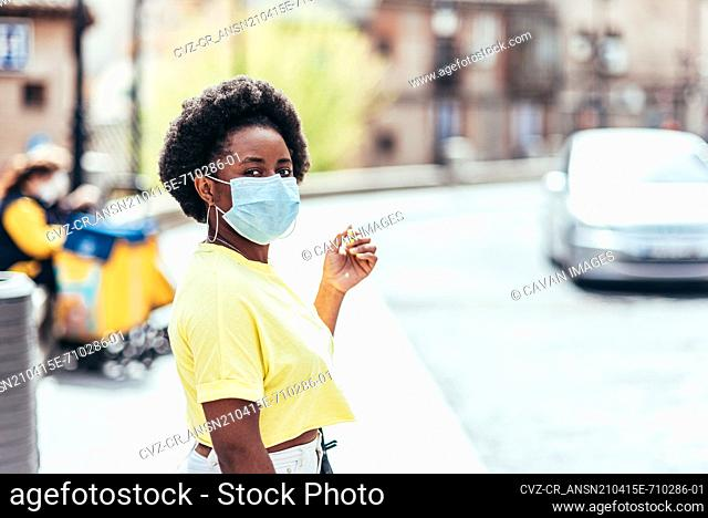 Portrait of black girl with face mask and afro hair waiting in an old city street