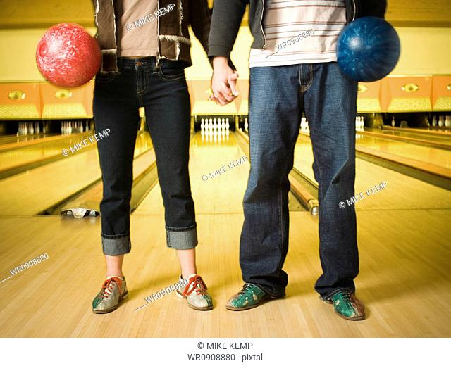 Waist down shot of male and female bowlers