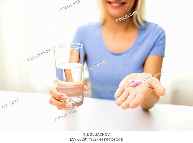 healthy eating, medicine, health care, food supplements and people concept - close up of woman hands holding pills and water glass at home