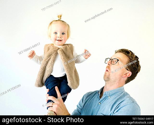 Portrait of father playing with daughter (2-3)