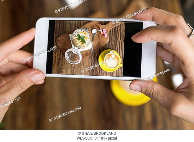 Female hands taking a picture of muesli and coffee with smartphone