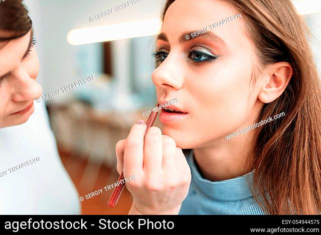 Make up artist hand with brush applying gloss on woman lips. Professional female beautician work with glamour attractive girl