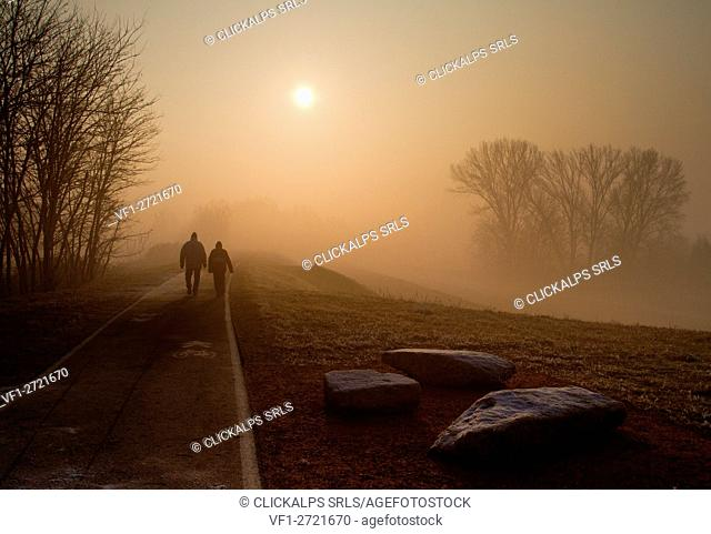 Europe, Italy, Veneto, Verona. Walking on riverbank of Adige during a foggy morning