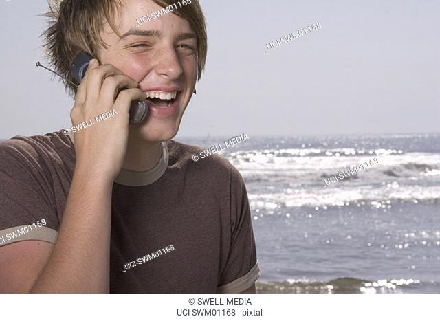 Teenage boy talking on cell phone at beach