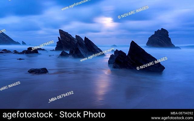 Moonlight on sandy beach with rock formations, Praia da Adraga, Sintra, Portugal