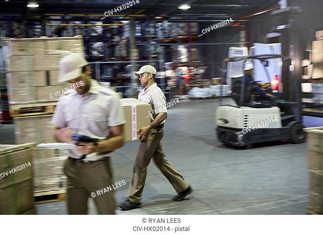 Workers carrying and moving boxes with forklift at distribution warehouse loading dock