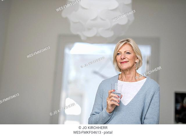 Portrait of relaxed senior woman with glass of water at home