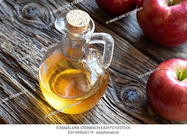 A bottle of apple cider vinegar on a rustic background