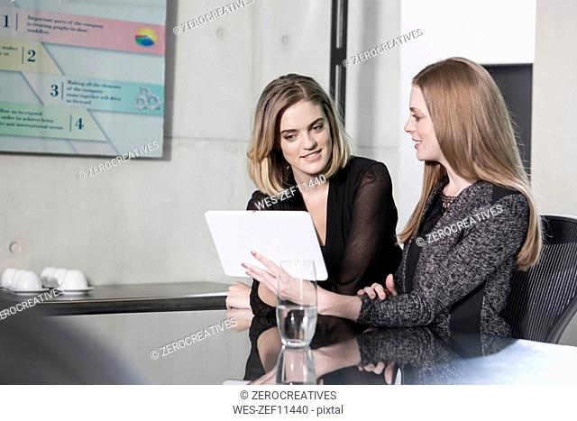 Businesswomen in meeting discussing in office, using digital tablet