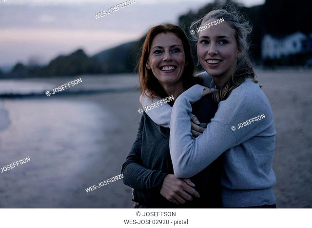 Germany, Hamburg, happy mother and teenage girl hugging on the beach at Elbe shore in the evening