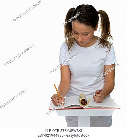 Young schoolgirl with her hair in pigtails sitting at a desk writing class notes in a red hardcover book