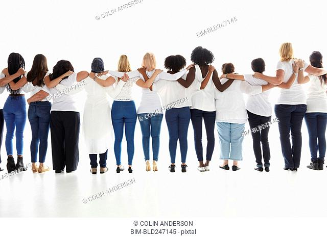 Rear view of diverse women standing in a row hugging
