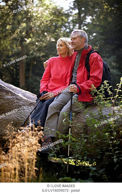 A mature couple sitting on a tree trunk looking at their surroundings
