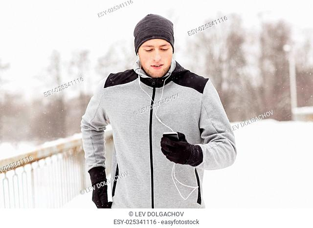 fitness, sport, people, technology and healthy lifestyle concept - young man in earphones with smartphone listening to music and running along winter road