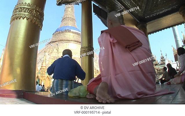 Buddhists meditate facing the Shwedagon Pagoda in Rangoon, Burma