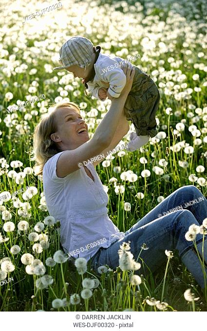Germany, Ammersee, Diessen, Mother playing with baby boy 2-3 in dandelion meadow