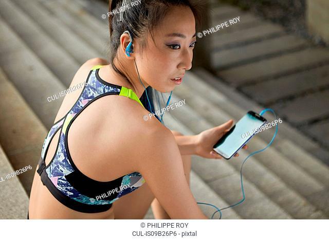 Woman sitting on steps wearing earphones holding smartphone
