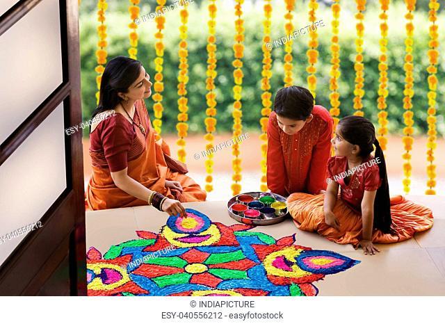 Woman making a rangoli while her children watch