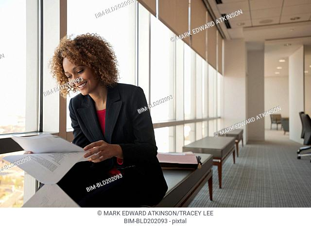 Mixed race businesswoman working in conference room