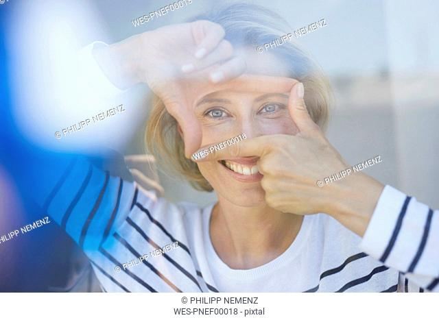 Portrait of laughing blond woman building frame with her fingers while looking at viewer