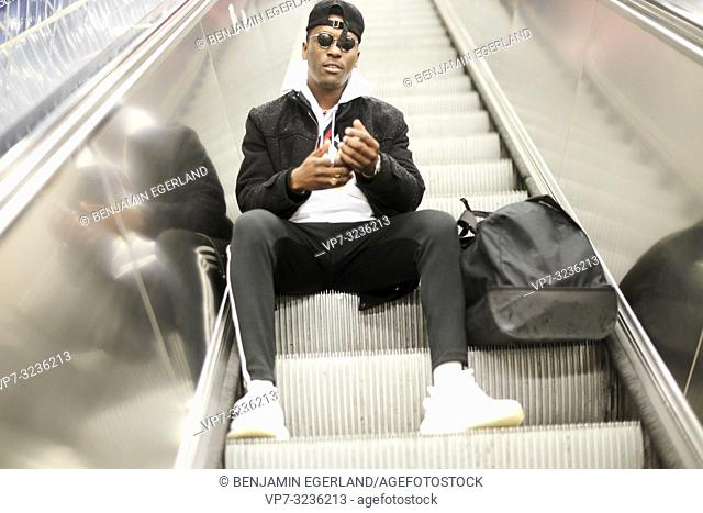 young man sitting on escalator, in Munich, Germany