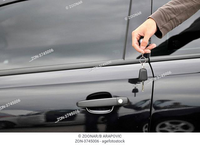 male hand holding car key with new black car in background