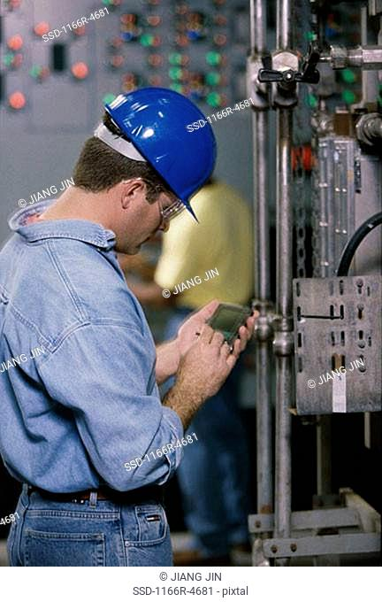 Worker standing beside machinery at a power plant operating a hand held device