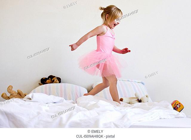 Girl dressed as ballet dancer running on bed