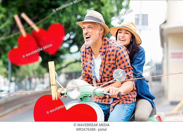 Couple riding on scooter against red hanging hearts