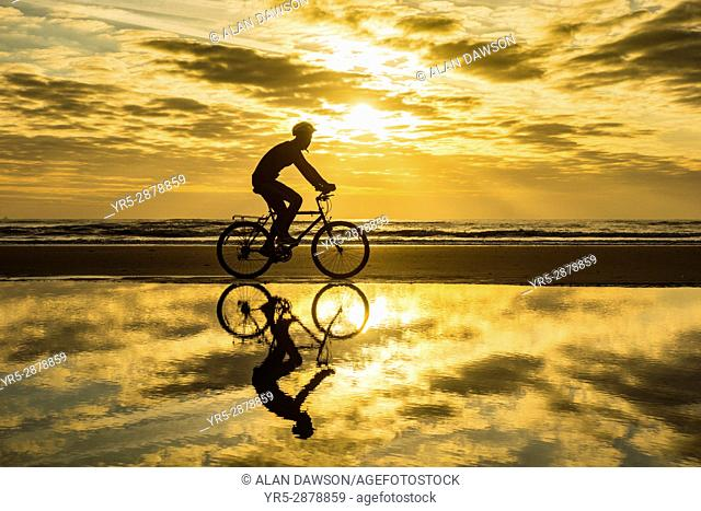 Seaton Carew, County Durham, north east England. United Kingdom. A mountain biker reflected in beach tidal pool at sunrise