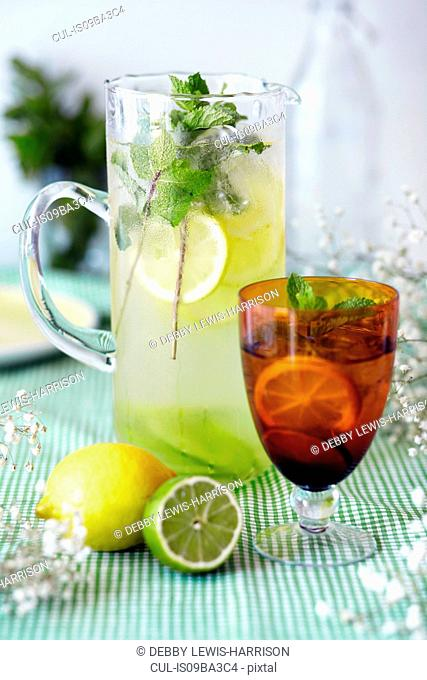 Jug and glass of lemon and lime cordial, with fresh fruit and ice, close-up