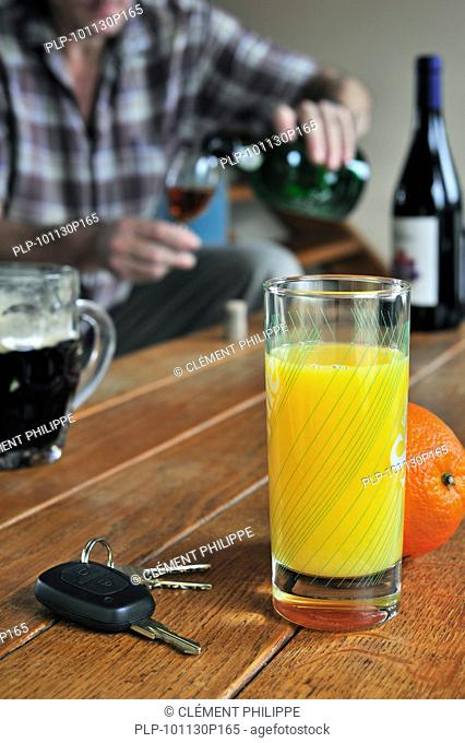 Car key, fruit juice and alcohol on table