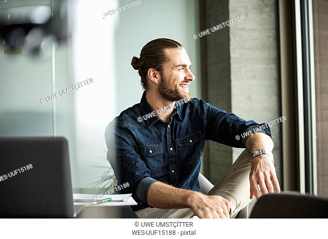 Smiling businessman sitting in office looking out of window
