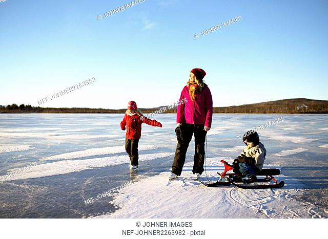 Mother with children skating on lake