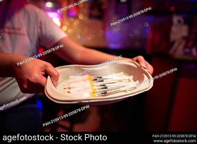 """13 September 2021, Hamburg: A member of the vaccination team holds a bowl with syringes in the bar """"""""Wunderbar"""""""" near the Reeperbahn in the St"""