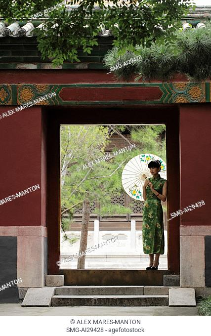 Young woman wearing Chinese traditional dress standing in doorway holding an umbrella