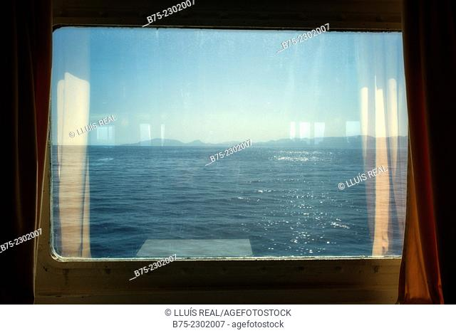 View of the sea with the island of Mallorca on the horizon through the window of a passenger ship. Balearic Islands, Mediterranean sea, Spain, Europe