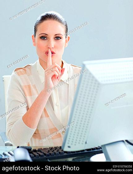 Attractive businesswoman at a computer asking for silence