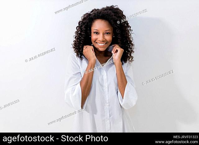 Young woman smiling while holding collar against white background