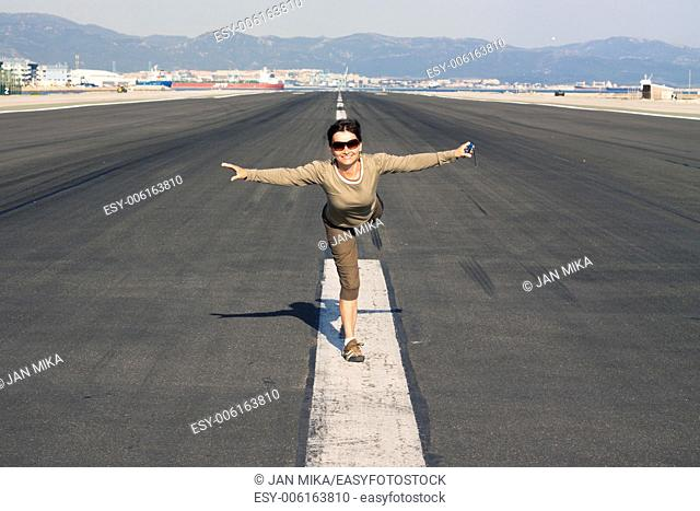 Happy woman tourist imitating airplane at the airport runway