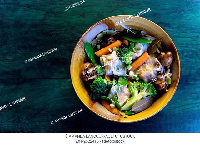 Overhead view of ceramic bowl styled with vegetable soup, stew on a greenish blue wood grain
