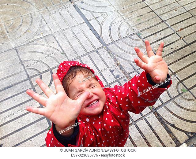 Pretty little girl having fun a rain day on street