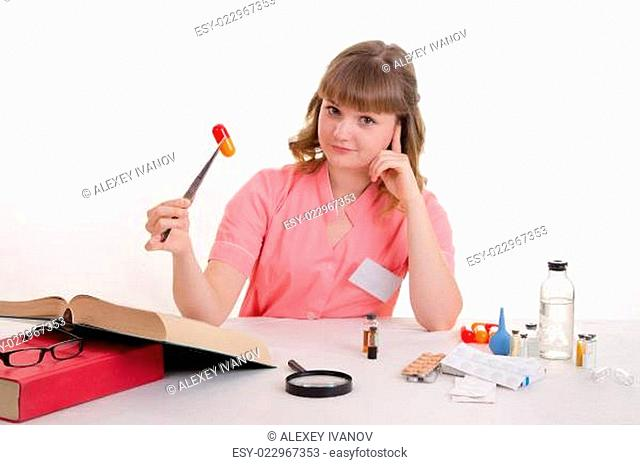 Medical student sitting at a table with tweezers on the pill