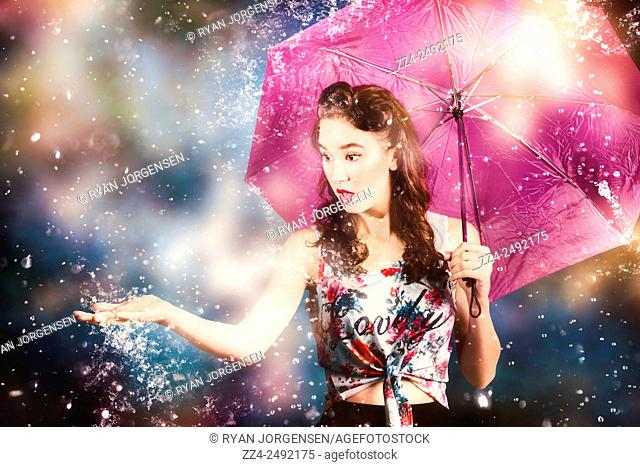 Colourful retro photo of a beautiful pin up woman catching a handful of water during a turbulent storm downpour. Sensing rain