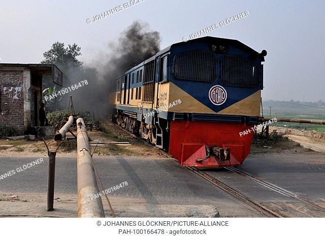 Railroad crossing and train with diesel locomotive 2803 near Narsingdi on 09.01.2015 - Bangladesh. | usage worldwide. - Narsingdi/Dhaka/Bangladesh