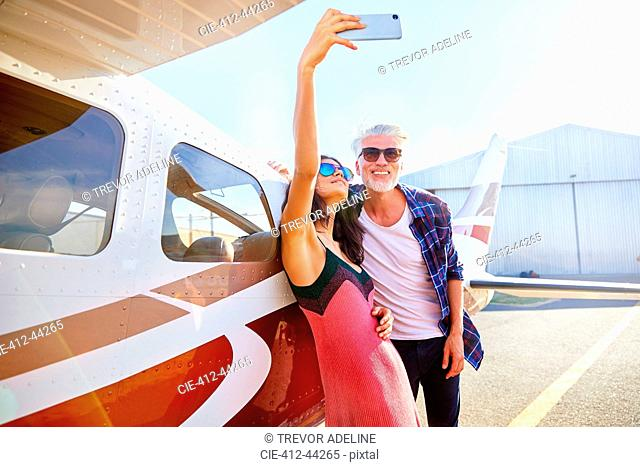 Couple taking selfie with camera phone at small airplane
